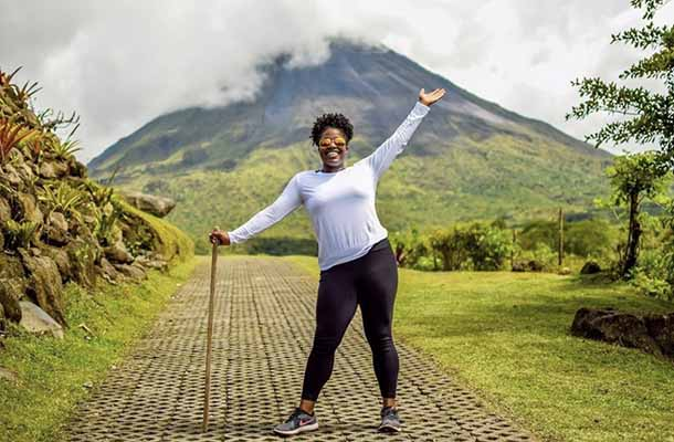 Student poses with Volcan Arenal in Costa Rica